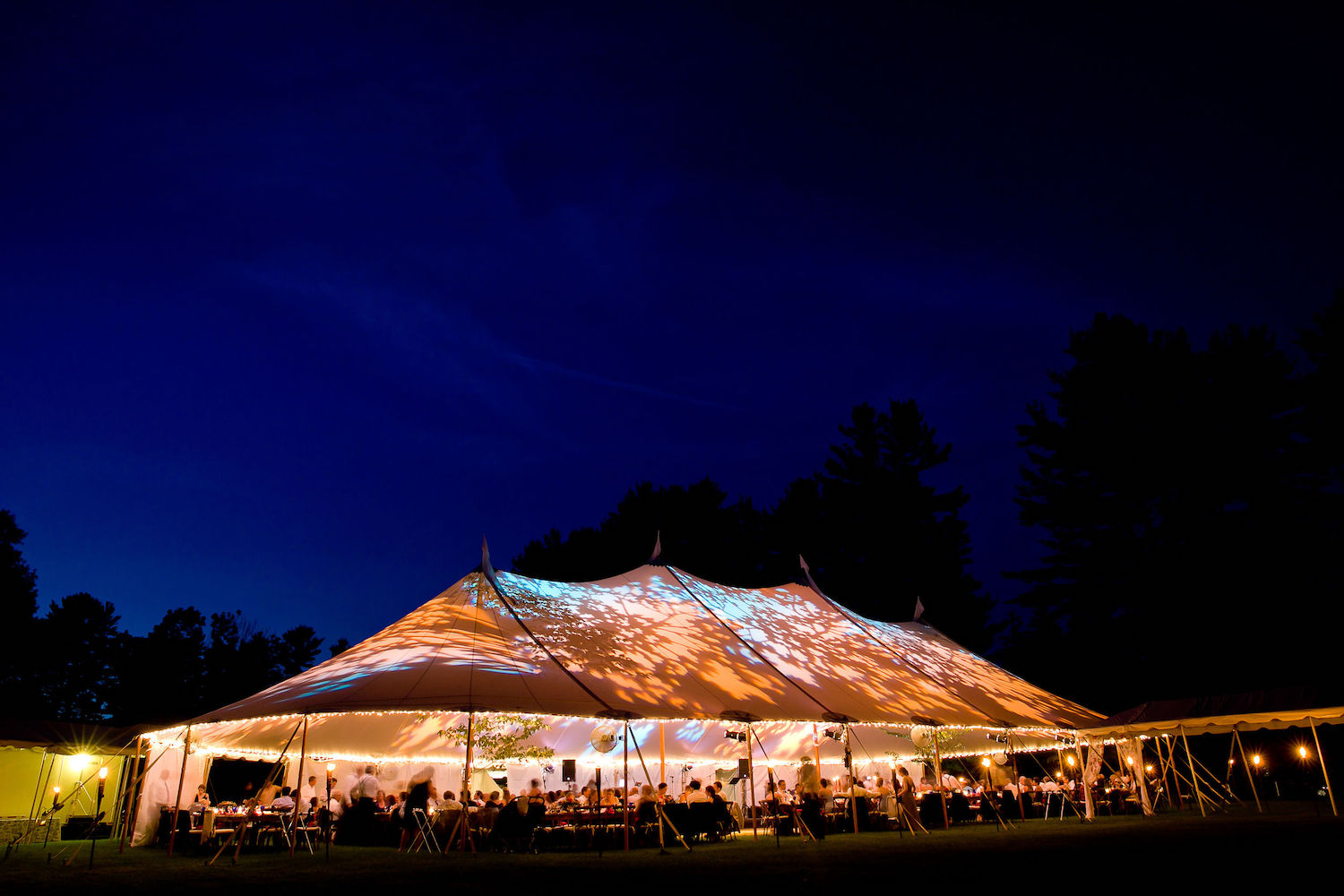 Wedding tent at night – Special event tent lit up from the inside with dark blue night time sky and trees